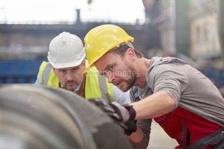 Focused male engineers examining steel part in factoryの写真素材 [FYI02944364]