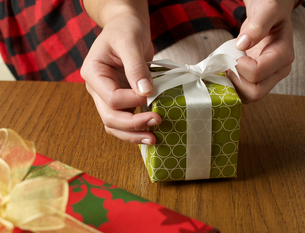 Close-Up of Woman Wrapping Christmas Presentの写真素材 [FYI02944383]
