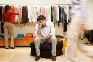Bored man in women's clothing storeの写真素材 [FYI02944407]