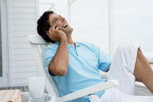 Happy man using mobile phone near beachの写真素材 [FYI02944490]