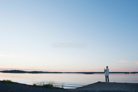 Sweden, Uppland, Stockholms Skargard, Graddo, Woman standing on beach and photographing landscape atの写真素材 [FYI02944496]