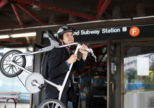 Businessman Carrying Bicycle to Subway Stationの写真素材 [FYI02944586]