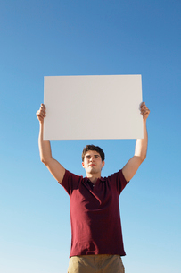 Young man holding blank piece of paperの写真素材 [FYI02944596]