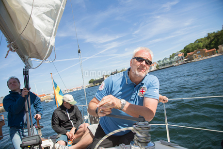 Sweden, West Coast, Bohuslan, Marstrand, Men sailing on lakeの写真素材 [FYI02944601]
