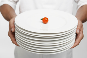 Chef holding dinner plates with a tomatoの写真素材 [FYI02944622]