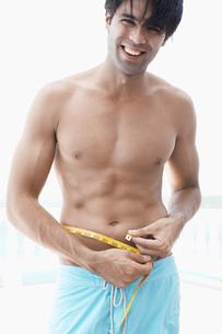 Young man measuring waistの写真素材 [FYI02944650]