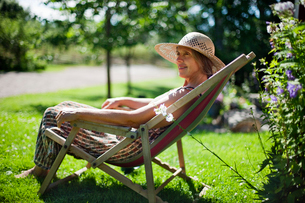 Sweden, Vastergotland, Tarby, Senior woman relaxing on sun cの写真素材 [FYI02944652]