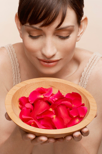 Mid adult woman holding bowl of petalsの写真素材 [FYI02944659]
