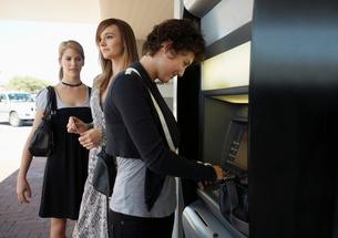 Teenage girls at cash machineの写真素材 [FYI02944663]
