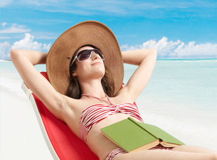 Woman Relaxing with Book on Stomachの写真素材 [FYI02944667]