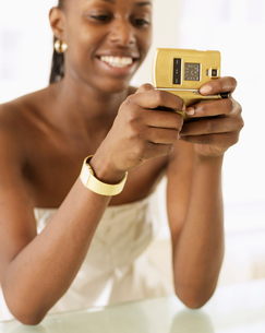 Woman Text Messaging with Golden Phoneの写真素材 [FYI02944738]