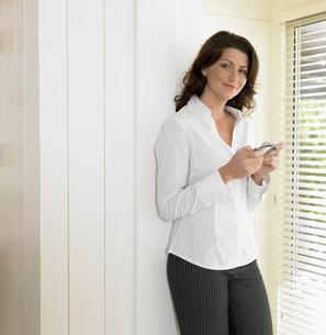 Woman using cell phone near windowの写真素材 [FYI02944742]