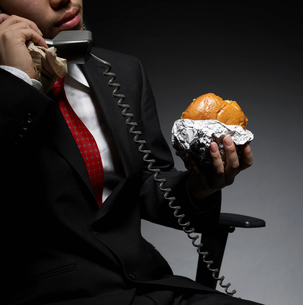 Businessman Having Lunch While on Phoneの写真素材 [FYI02944758]