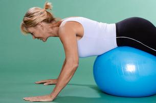 Mature woman exercising on Swiss ballの写真素材 [FYI02944761]