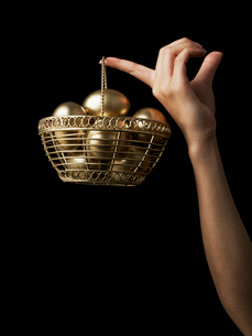 Golden Egg Basket Hanging From Fingerの写真素材 [FYI02944771]