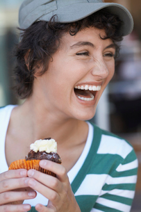 Teenage girl laughing and eating cakeの写真素材 [FYI02944779]