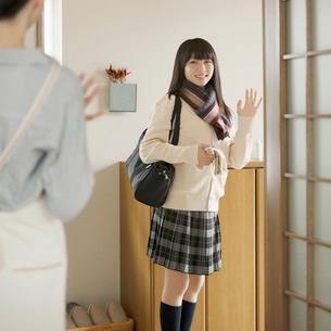 玄関で手を振る女子学生の写真素材 [FYI02944820]