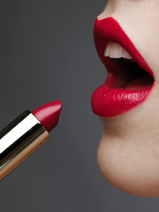 Woman applying lipstickの写真素材 [FYI02944834]