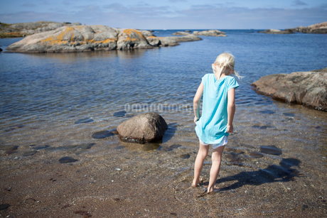 Sweden, Bohuslan, Archipelago of Gothenburg, Ockero, Girl standing ankle deep in waterの写真素材 [FYI02944839]