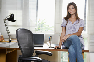 Young entrepreneur sitting on deskの写真素材 [FYI02944844]