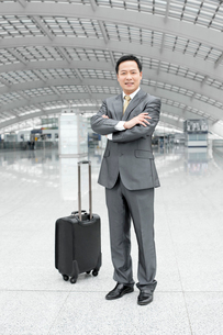Mature businessman with arms crossed in airport lobbyの写真素材 [FYI02944878]
