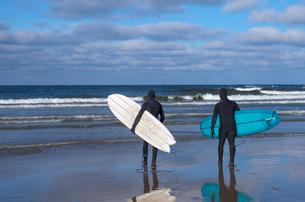 Finland, Pohjanmaa, Vexala, Rear view of surfers in wetsuits on beachの写真素材 [FYI02944880]