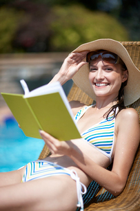 Happy Woman Reading Book by Poolの写真素材 [FYI02944911]