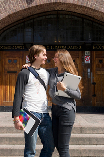 Sweden, Stockholm, Ostermalm, Students embracing on stairs in front of school buildingの写真素材 [FYI02944949]