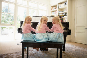 Triplets playing piano in living roomの写真素材 [FYI02944959]