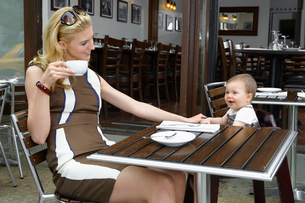 Mid adult mother with baby girl in caf?の写真素材 [FYI02945009]