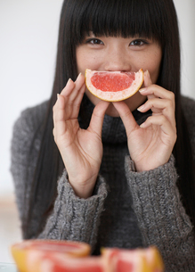 Mid-Adult Woman Eating  Pink Grapefruitの写真素材 [FYI02945011]