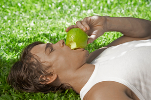 Young man eating apple on lawnの写真素材 [FYI02945012]