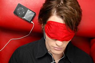 Man with sleep mask listening to musicの写真素材 [FYI02945065]