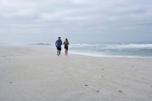 Mid adult couple running on sandy beachの写真素材 [FYI02945090]
