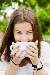 Sweden, Sodermanland, Stockholm, Portrait of young woman drinking from cup in parkの写真素材 [FYI02945106]