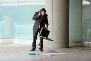 Man on phone with documents on floorの写真素材 [FYI02945112]