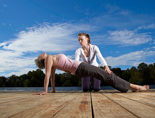 Young woman teaching mature woman yogaの写真素材 [FYI02945120]