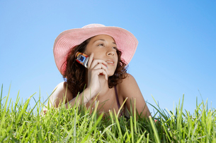 Woman with cell phone lying on grassの写真素材 [FYI02945130]