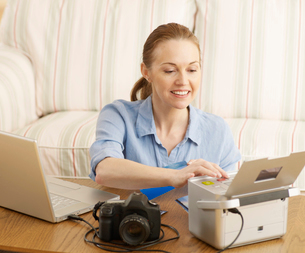 Woman Printing Out Digital Photographsの写真素材 [FYI02945132]