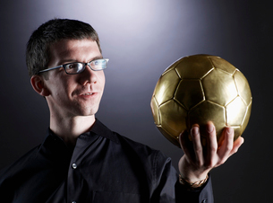 Man Holding Golden Soccer Ballの写真素材 [FYI02945146]