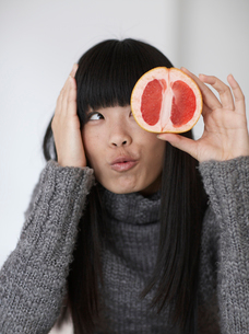 Mid-Adult Woman Eating  Pink Grapefruitの写真素材 [FYI02945236]