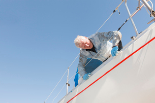 Sweden, Sodermanland, Jarna, Man maintaining sailboatの写真素材 [FYI02945244]