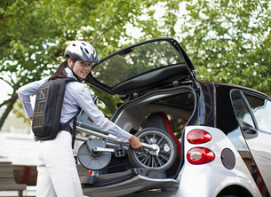 Mid-Adult Woman Putting Bicycle into Car Trunkの写真素材 [FYI02945272]