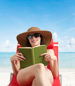 Young Woman Reading Book on Lounge Chairの写真素材 [FYI02945274]