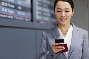 Young businesswoman holding passport and smart phone in airportの写真素材 [FYI02945285]