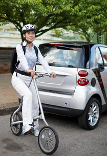 Mid-Adult Woman on Bicycle Beside Smart Carの写真素材 [FYI02945324]