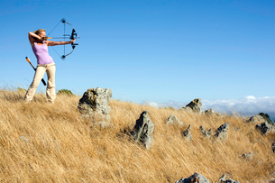Young woman arrow shooting in fieldの写真素材 [FYI02945330]