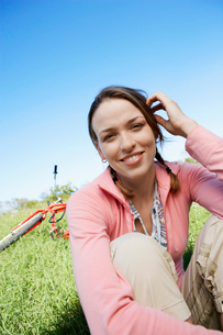 Young woman with bicycle sitting on lawnの写真素材 [FYI02945339]
