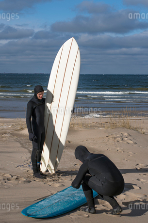 Finland, Pohjanmaa, Vexala, Surfers in wetsuits on beachの写真素材 [FYI02945349]