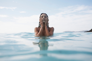 Young woman applying mud mask in waterの写真素材 [FYI02945353]